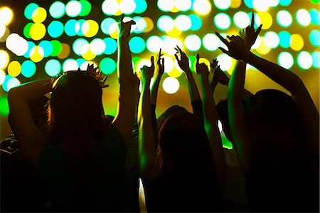 silhouette hand - Audience watching a rock show, hands in the air, rear view, stage lights Stock Photo - Premium Royalty-Free, Code: 6116-07236051