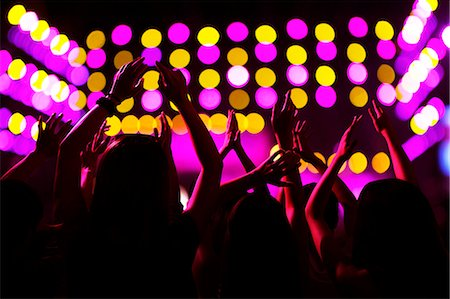 Audience watching a rock show, hands in the air, rear view, stage lights Stock Photo - Premium Royalty-Free, Code: 6116-07236052