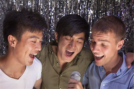 Three friends with arm around each other holding a microphone and singing together at karaoke Stock Photo - Premium Royalty-Free, Code: 6116-07236064