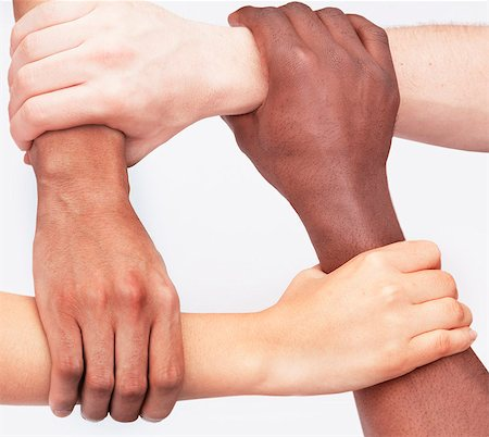 Four young people holding each others wrists in a circle, close-up, studio shot Stock Photo - Premium Royalty-Free, Code: 6116-07236006