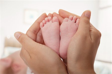 female feet close up - Close-up of mother holding her baby's feet Stock Photo - Premium Royalty-Free, Code: 6116-07236020
