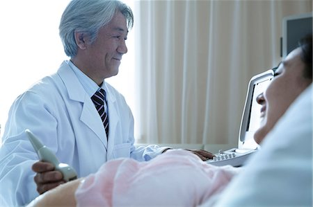 pregnant asian - Doctor doing an ultrasound on a pregnant woman lying on her back in the hospital Stock Photo - Premium Royalty-Free, Code: 6116-07236183