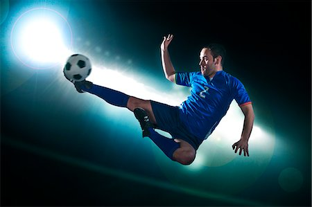 soccer player (male) - Soccer player in mid air kicking the soccer ball, stadium lights at night in background Stock Photo - Premium Royalty-Free, Code: 6116-07236119