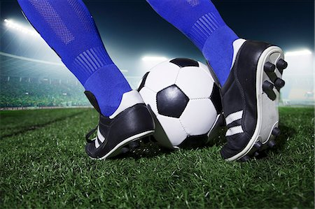 soccer player (male) - Close up of feet kicking the soccer ball, night time in the stadium Stock Photo - Premium Royalty-Free, Code: 6116-07236138