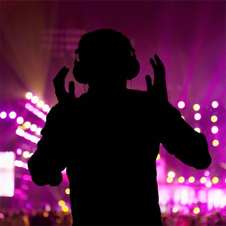 Silhouette of DJ wearing headphones and performing at a night club Stock Photo - Premium Royalty-Free, Code: 6116-07236255