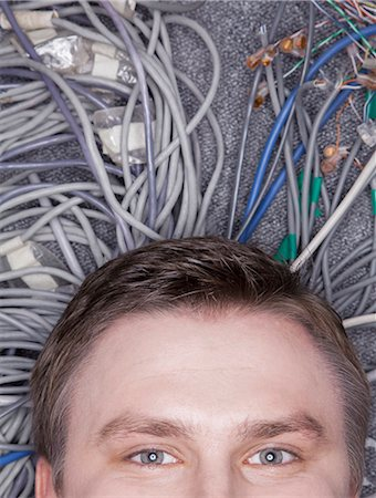 Businessman's face lying down on computer cables looking up, half Stock Photo - Premium Royalty-Free, Code: 6116-07236259