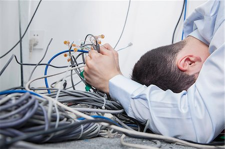 Frustrated man lying down trying to figure out and sort  computer cables Stock Photo - Premium Royalty-Free, Code: 6116-07236262