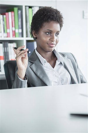 portrait looking away - Portrait of young smiling businesswoman sitting at a table and holding a pen Stock Photo - Premium Royalty-Free, Code: 6116-07236264