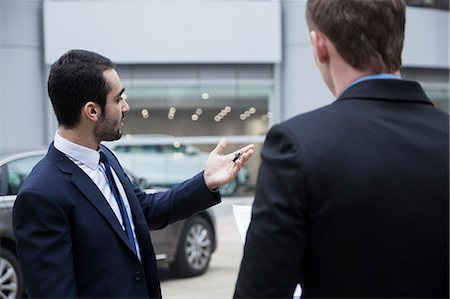 sale - Car salesman holding car keys and selling a car to a young businessman Stock Photo - Premium Royalty-Free, Code: 6116-07236284