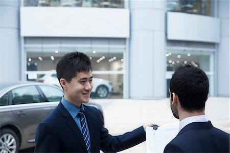 sale - Car salesman holding car keys and paperwork and selling a car to a young businessman Stock Photo - Premium Royalty-Free, Code: 6116-07236285