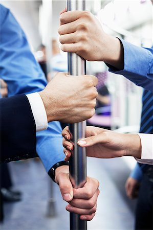 Close-up of four business people's hands holding the pole on the subway Stock Photo - Premium Royalty-Free, Code: 6116-07236297