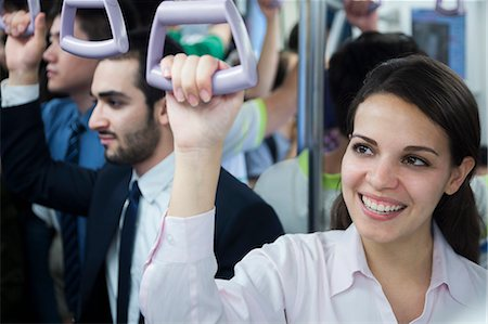 Portrait of smiling young businesswoman standing on the subway, looking away Stock Photo - Premium Royalty-Free, Code: 6116-07236296