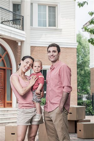 Portrait of smiling family in front of their new home Stock Photo - Premium Royalty-Free, Code: 6116-07236222