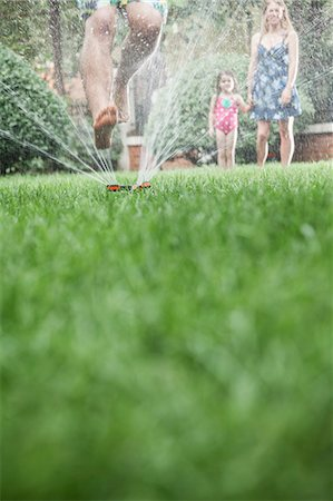 Surface level shot of father jumping through a sprinkler in the grass, mother and daughter watch in the background Stock Photo - Premium Royalty-Free, Code: 6116-07236227
