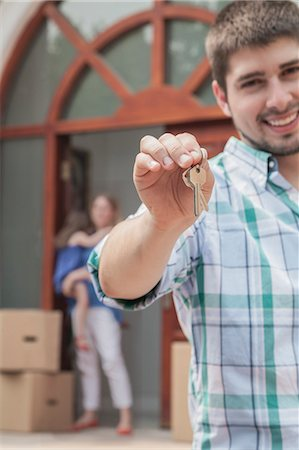 Father smiling and holding the keys to the new house, family in the background Stock Photo - Premium Royalty-Free, Code: 6116-07236224