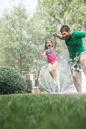 Father holding daughters hand while she jumps through the sprinkler in the garden Stock Photo - Premium Royalty-Free, Code: 6116-07236226