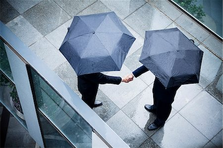 people with umbrellas in the rain - High angle view of two businessmen holding umbrellas and shaking hands in the rain Stock Photo - Premium Royalty-Free, Code: 6116-07236378
