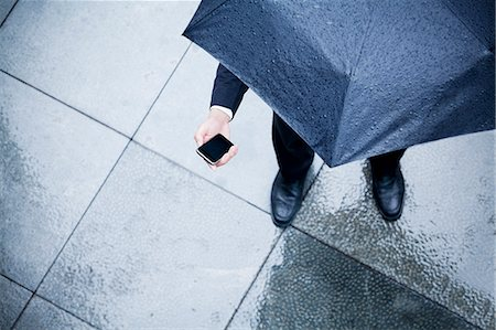 people with umbrellas in the rain - High angle view of businessman holding an umbrella and looking at his phone in the rain Stock Photo - Premium Royalty-Free, Code: 6116-07236380