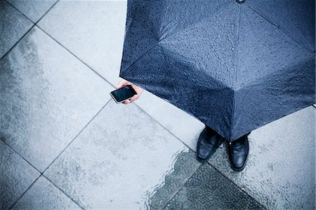people with umbrellas in the rain - High angle view of businessman holding an umbrella and looking at his phone in the rain Stock Photo - Premium Royalty-Free, Code: 6116-07236381
