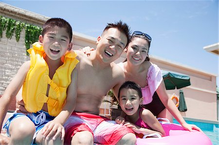 swimming pool water - Family portrait, mother, father, daughter, and son, smiling by the pool Stock Photo - Premium Royalty-Free, Code: 6116-07236312