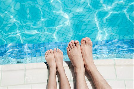 Close up of two people's legs by the pool side Stock Photo - Premium Royalty-Free, Code: 6116-07236315