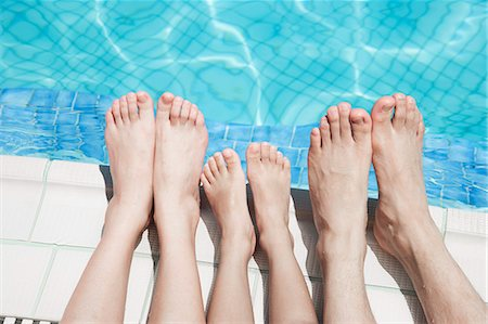 Close up of three people's legs by the pool side Stock Photo - Premium Royalty-Free, Code: 6116-07236316