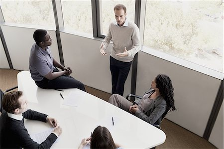 partnership - Five business people sitting at a conference table and discussing during a business meeting Stock Photo - Premium Royalty-Free, Code: 6116-07236445