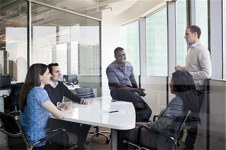 Five business people sitting at a conference table and discussing during a business meeting Stock Photo - Premium Royalty-Free, Code: 6116-07236446