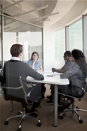 Four business people sitting at a conference table and discussing during a business meeting Stock Photo - Premium Royalty-Free, Code: 6116-07236449