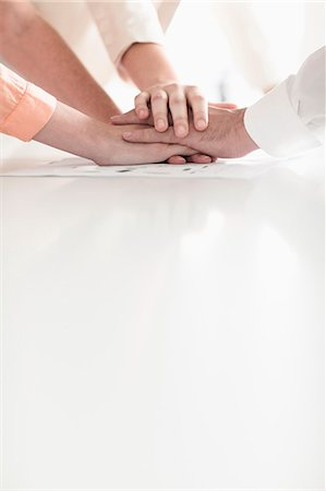 Close up of hands of business people on top of each other in partnership Stock Photo - Premium Royalty-Free, Code: 6116-07236474