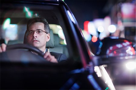 Businessman driving at night in the city Stock Photo - Premium Royalty-Free, Code: 6116-07236493