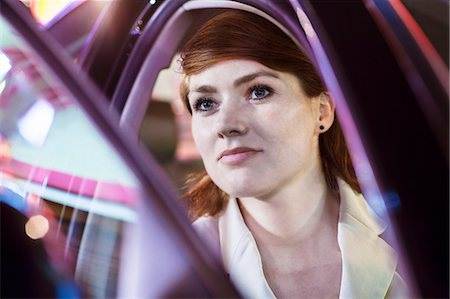 Serene businesswoman opening car door at night, close-up, reflected lights Stock Photo - Premium Royalty-Free, Code: 6116-07236490