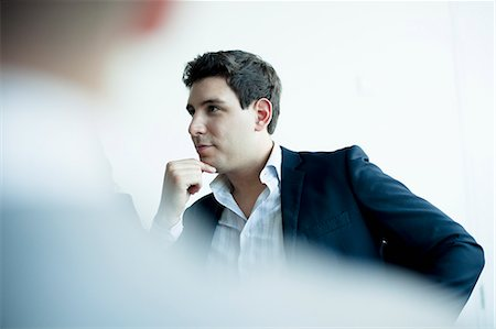 Young businessman listening in a business meeting Stock Photo - Premium Royalty-Free, Code: 6116-07236585