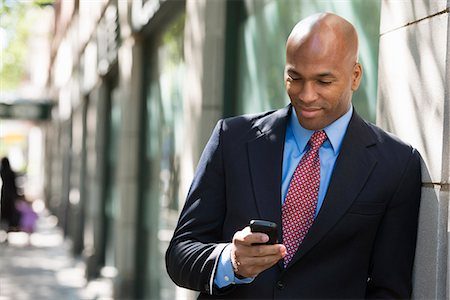 settlement - Business People. A Businessman In A Suit And Red Tie, Checking His Phone. Stock Photo - Premium Royalty-Free, Code: 6118-07121997