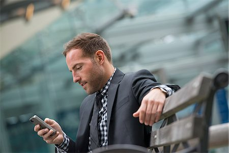 settlement - Business People. A Man In A Business Suit. A Man With Short Red Hair And A Beard, Wearing A Suit, On His Phone. Stock Photo - Premium Royalty-Free, Code: 6118-07121910