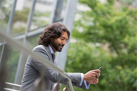 settlement - Business People. A Man In A Suit With Brown Curly Hair And A Beard. On His Phone. Stock Photo - Premium Royalty-Free, Code: 6118-07121920