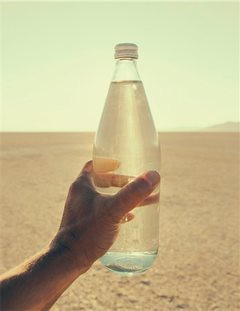 The Landscape Of The Black Rock Desert In Nevada. A Man's Hand Holding A Bottle Of Water. Filtered Mineral Water. Stock Photo - Premium Royalty-Free, Code: 6118-07122053