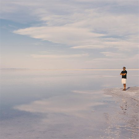 A Man Standing At Edge Of The Flooded Bonneville Salt Flats At Dusk. Arms Folded. Stock Photo - Premium Royalty-Free, Code: 6118-07122065