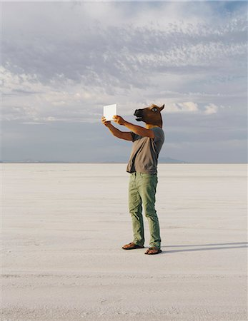 A Man Wearing A Horse Mask, Taking A Photograph With A Tablet Device, On Bonneville Salt Flats. Stock Photo - Premium Royalty-Free, Code: 6118-07122080