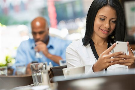 settlement - Business People. Two People Sitting At Coffee Shop Tables, Checking Their Messages. Stock Photo - Premium Royalty-Free, Code: 6118-07122002