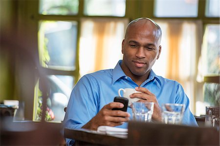settlement - Business People. A Man Sitting Checking His Phone. Stock Photo - Premium Royalty-Free, Code: 6118-07122004