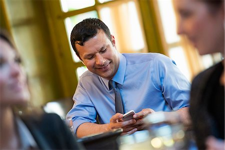 settlement - Business People. Three People Around A Cafe Table, One Of Whom Is Checking Their Phone. Stock Photo - Premium Royalty-Free, Code: 6118-07122016