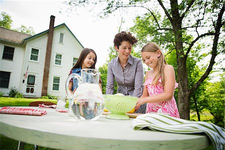 A Summer Family Gathering At A Farm. A Woman And Two Children Standing Outside By A Table, Laying The Table. Making Lemonade. Stock Photo - Premium Royalty-Free, Code: 6118-07122147