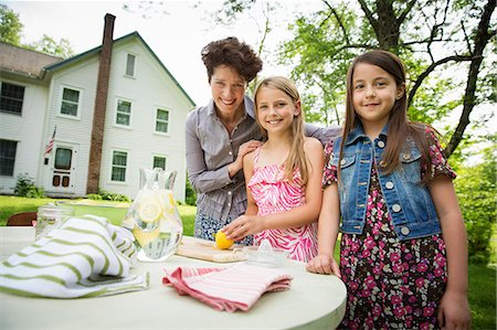 A Summer Family Gathering At A Farm. A Woman And Two Children Standing Outside By A Table, Laying The Table. Making Lemonade. Stock Photo - Premium Royalty-Free, Code: 6118-07122148