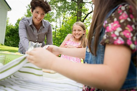 A Summer Family Gathering At A Farm. A Woman And Two Children Standing Outside By A Table, Laying The Table. Stock Photo - Premium Royalty-Free, Code: 6118-07122149
