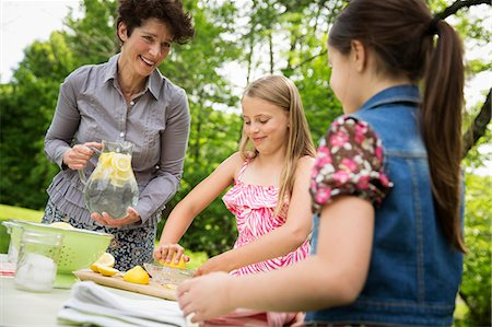 A Summer Family Gathering At A Farm. A Woman And Two Children Standing Outside By A Table, Laying The Table. Making Lemonade. Stock Photo - Premium Royalty-Free, Code: 6118-07122151