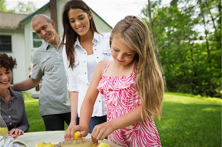 A Summer Family Gathering At A Farm. A Girl Slicing And Juicing Lemons To Make Lemonade. Stock Photo - Premium Royalty-Free, Code: 6118-07122157