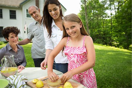 A Summer Family Gathering At A Farm. A Girl Slicing And Juicing Lemons To Make Lemonade. Stock Photo - Premium Royalty-Free, Code: 6118-07122158