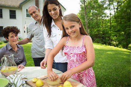 A Summer Family Gathering At A Farm. A Girl Slicing And Juicing Lemons To Make Lemonade. Stock Photo - Premium Royalty-Free, Code: 6118-07122158