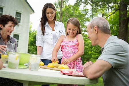 A Summer Family Gathering At A Farm. A Girl Slicing And Juicing Lemons To Make Lemonade. Stock Photo - Premium Royalty-Free, Code: 6118-07122159